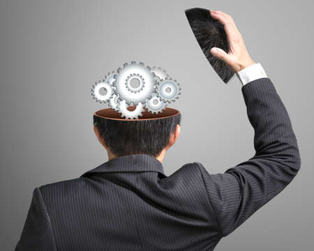 Working metal gears inside business head on gray background Stock Photo - 22417456