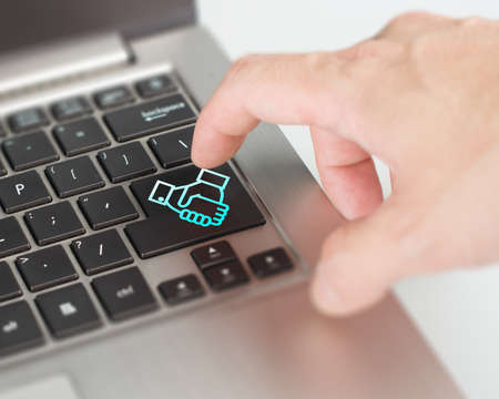 online dealing and cooperating concept push shake hand button and deal via internet Stock Photo - 22410864