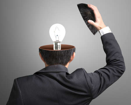 Single lighting lamp inside businessman head in gray background Stock Photo - 22410893