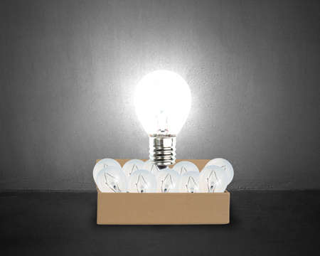 Big glowing light bulb float over opened cardboard box with many smaller bulbs in concrete wall background Stock Photo