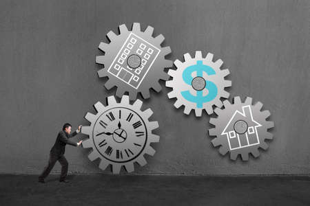 Businessman rolling a large concrete gear connect with others  each with clock, office, home and money drawing in concrete wall background  Archivio Fotografico