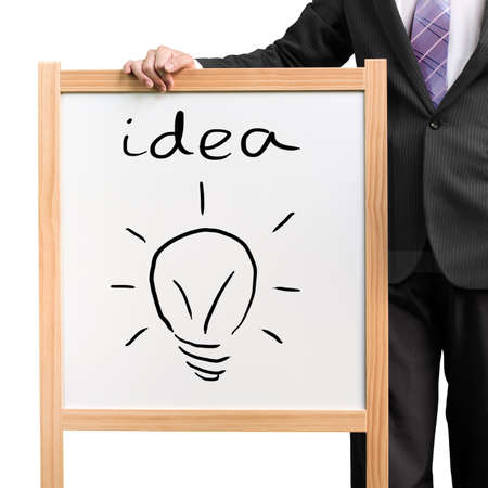 Businessman hold wooden white board with word idea and drawing lighting blub in white background photo