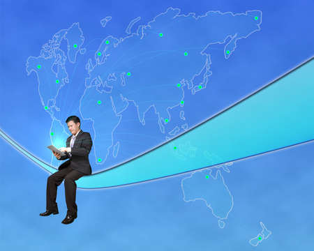 Businessman sitting and touch tablet with worldwide map background in blue sky photo