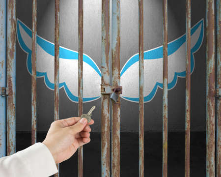 incarcerate: Hand hold key unlocking locked door with blue and white wings in gray concrete background