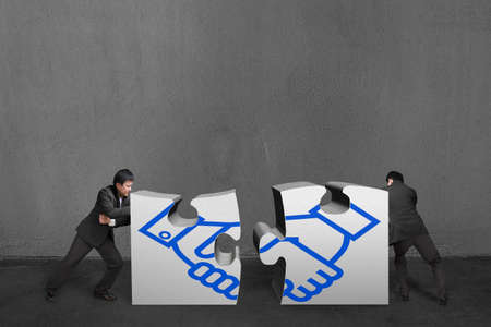 Businessmen push two heavy puzzles together with shake hand drawing in concrete wall background