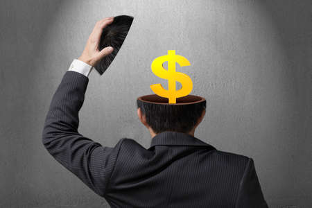 Golden money symbol inside businessman head in gray concrete wall background
