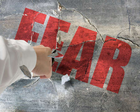 unafraid: Punching, break concrete wall with word fear on it and small pieces flying out