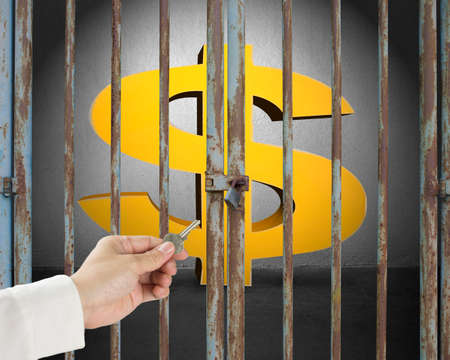 locked in: Hand hold key opening locked door with golden money symbol in gray concrete wall background Stock Photo