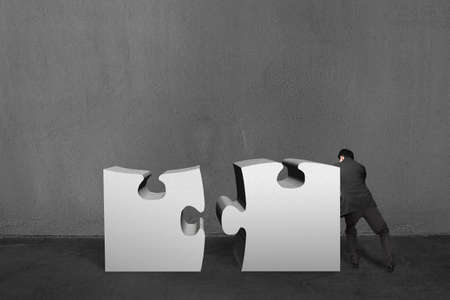 Businessman push two heavy puzzles together in concrete wall background photo