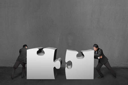 Businessmen push two heavy puzzles together in concrete wall background.