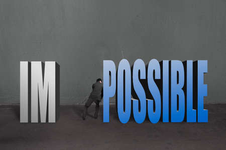 infeasible: Businessman push word impossible possible to separate, to make it possible in concrete wall background.