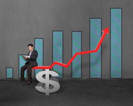 Businessman using tablet sitting on growth red arrow with money supporter and chart in concrete wall background photo
