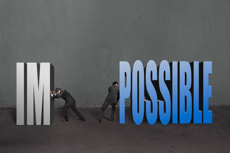 infeasible: Two businessmen separate word impossible to IM and POSSIBLE; to make it possible in concrete wall background.