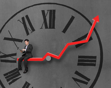 Businessman using tablet and sitting on growth red arrow with clock face in concrete wall background photo
