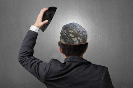 unyielding: Hard stone covered with lines inside businessman head in gray concrete wall background Stock Photo