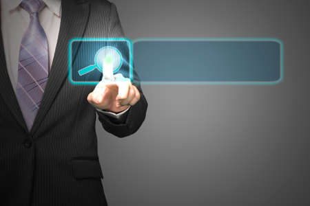 Businessman pushing on future touch screen with magnifier icon in space for searching in dark background