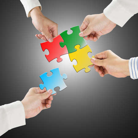 Team work concept, Hands hold puzzles connect each other with gray background