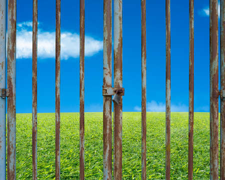 land locked: Locked rusty door with beautiful landscape, green meadow blue sky and cloud