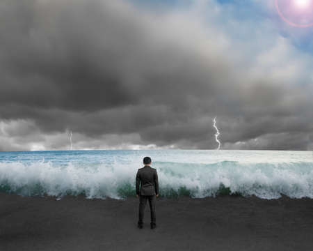 chellange: Businessman standing toward waves and cludy sky with Lightning , thunder to challenge dangerous situation