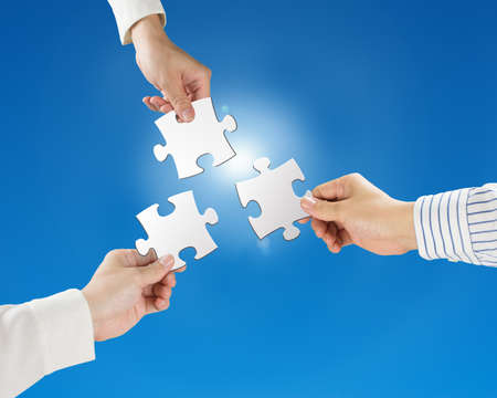 Team work concept, Hands hold puzzles with clear blue sky and sun light background  photo
