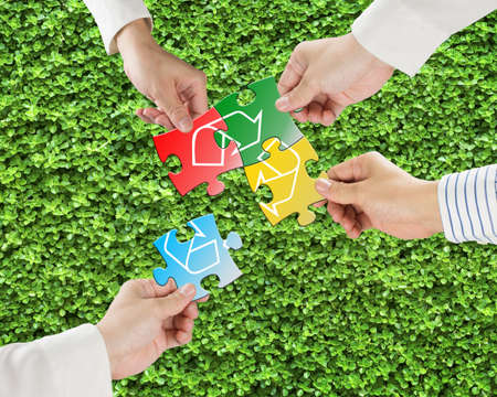 Hands hold puzzles with recycle symbol in fresh green meadow background  Stock Photo