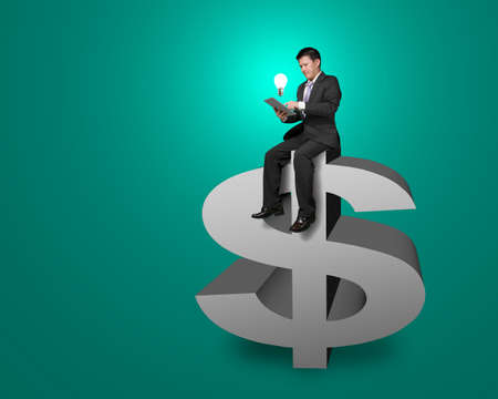 Businessman sitting on the top of money symbol with tablet and lighting bulb in green background photo