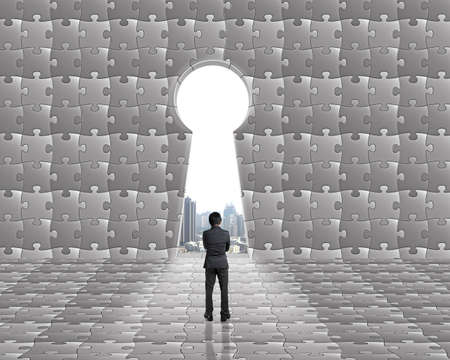 key hole shape: Businessman stand toward key hole shape door on puzzles wall with city view outside background Stock Photo