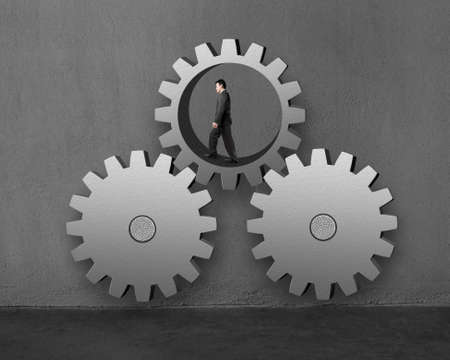 harmonization: Businessman walking inside large gear connecting with others in concrete wall background