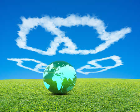 Big Green Ball with world wide map in recycling symbol shape clouds, fresh green meadow and blue sky background photo