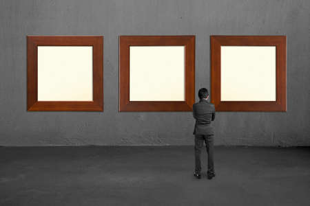 Businessman standing and looking at three blank wooden frames on concrete wall Stock Photo