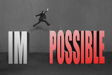 infeasible: Businessman jumping to possible from im, make it possible in concrete background