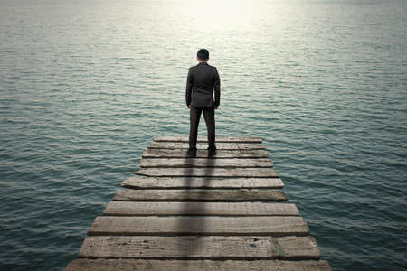 preoccupied: Businessman standing and thinking on old wooden pier to the sea with sunlight reflection