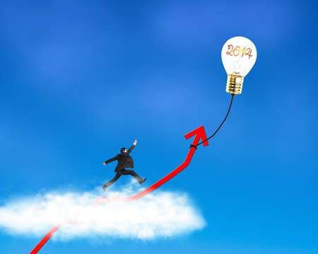 Businessman running on growth red arrow with glowing lamp balloon, through cloud in the sky Stock Photo