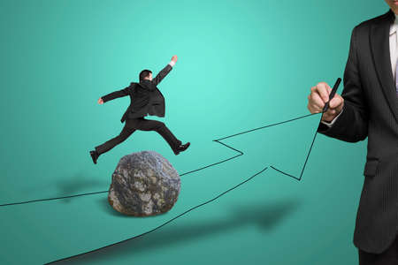 another way: Businessman drawing road with growing arrow, another jumping over large rock on the way Stock Photo