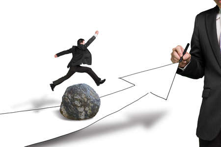 financial obstacle: Businessman drawing road with growing arrow, another jumping over large rock on the way Stock Photo