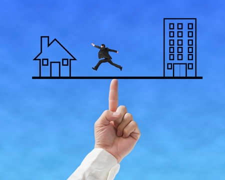 Office and home on seesaw drawing with index finger to balance, one businessman running on Stock Photo