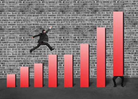 Businessman running and jumping on red bar chart another lift one with bricks wall background
