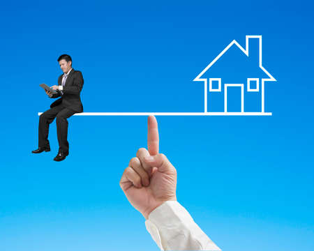 work life balance: Businessman sitting on seesaw with home balance by index finger  in blue sky background Stock Photo