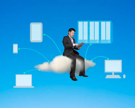 Businessman sitting and touch tablet with cloud computing background in blue sky Stock Photo
