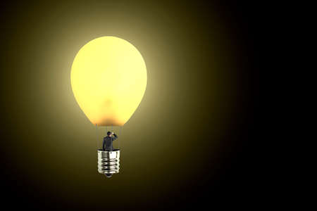 Man taking glowing lamp balloon looking at distant place, in  dark background photo