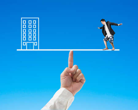 achievable: Businessman surfing on seesaw with Office, for index finger to balance, working and vacation balance concept
