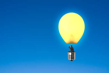Man taking glowing lamp balloon looking at distant place with blue sky background