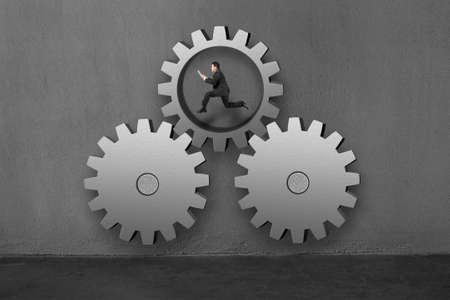 achievable: Businessman running inside large gear connecting with others with concrete wall background