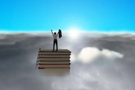 Businessman standing on top of stack of books with cloudy below and blue sky, sunlight photo