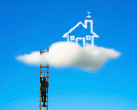 Businessman climbing on wooden ladder to reach cloud house with clear blue sky photo