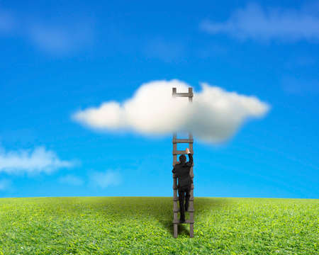 Businessman climbing on wooden ladder to reach cloud with green meadow and blue sky Stock Photo