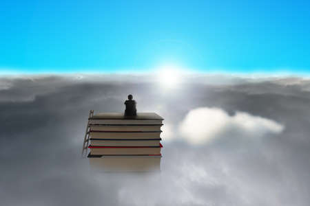 Businessman sitting on stack of books over cloudy face sun and blue sky Stock Photo