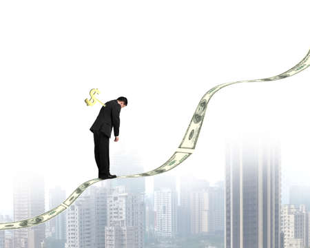 Businessman with money symbol winder on his back standing on growing money trend with city view Stock Photo