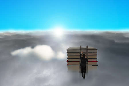 Businessman climbing on wooden ladder to top of stack books with cloudy below, sun and blue sky