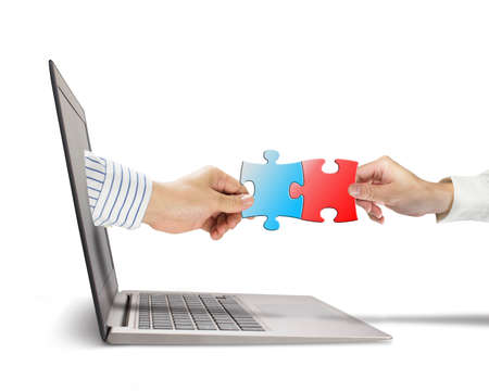 Hand holding puzzle coming out from screen to connect with another in white